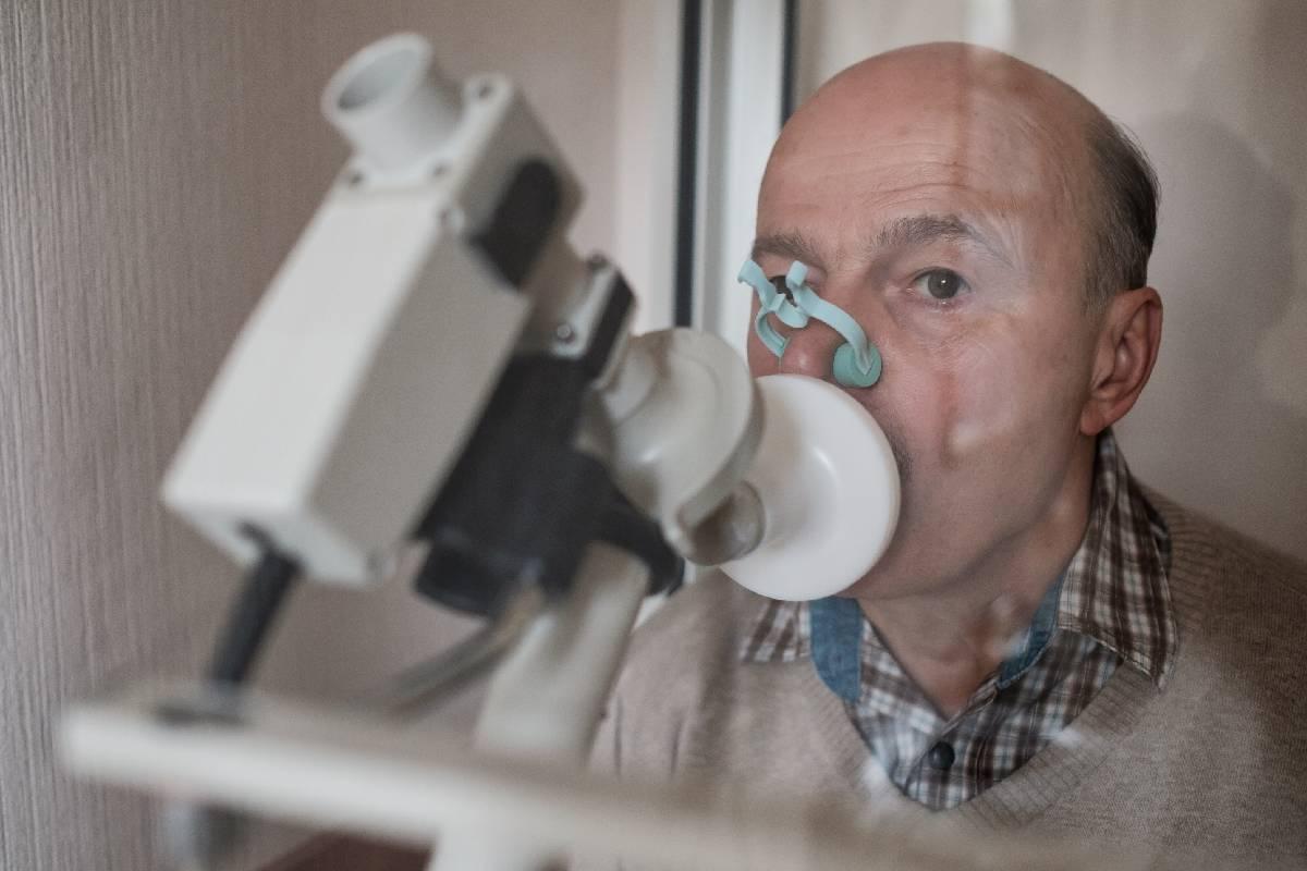 Senior hispanic man man testing breathing function by spirometry. Diagnosis of respiratory function in pulmonary disease