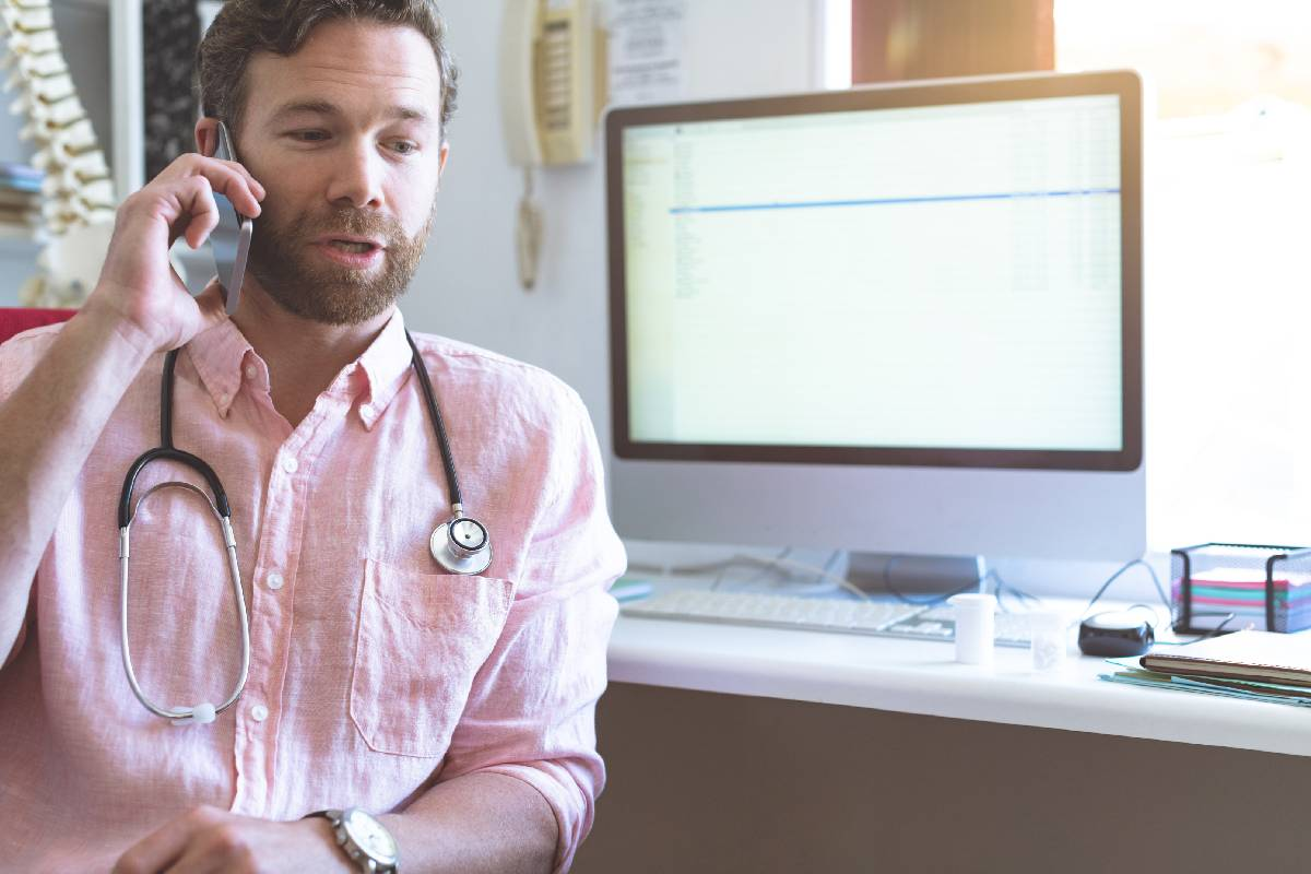 Front view of a Caucasian male doctor talking on mobile phone in clinic against computer in background